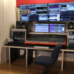 Empty office chair in front of a large display of audio equipment