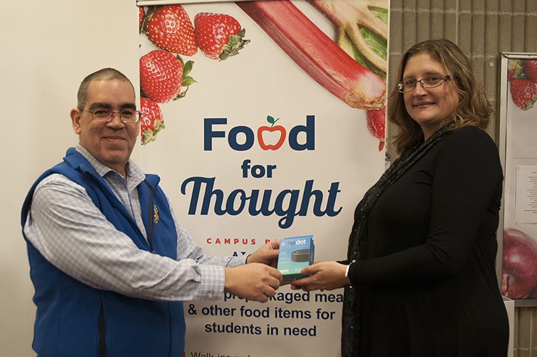MWCC Assistant Professor of Business Geraldo Maldonado stands with Director of the Senator Stephen M. Brewer Center for Civic Learning Shelley Nicholson holding the Echo Dot Maldonado won as part of the Do One Thing campaign.