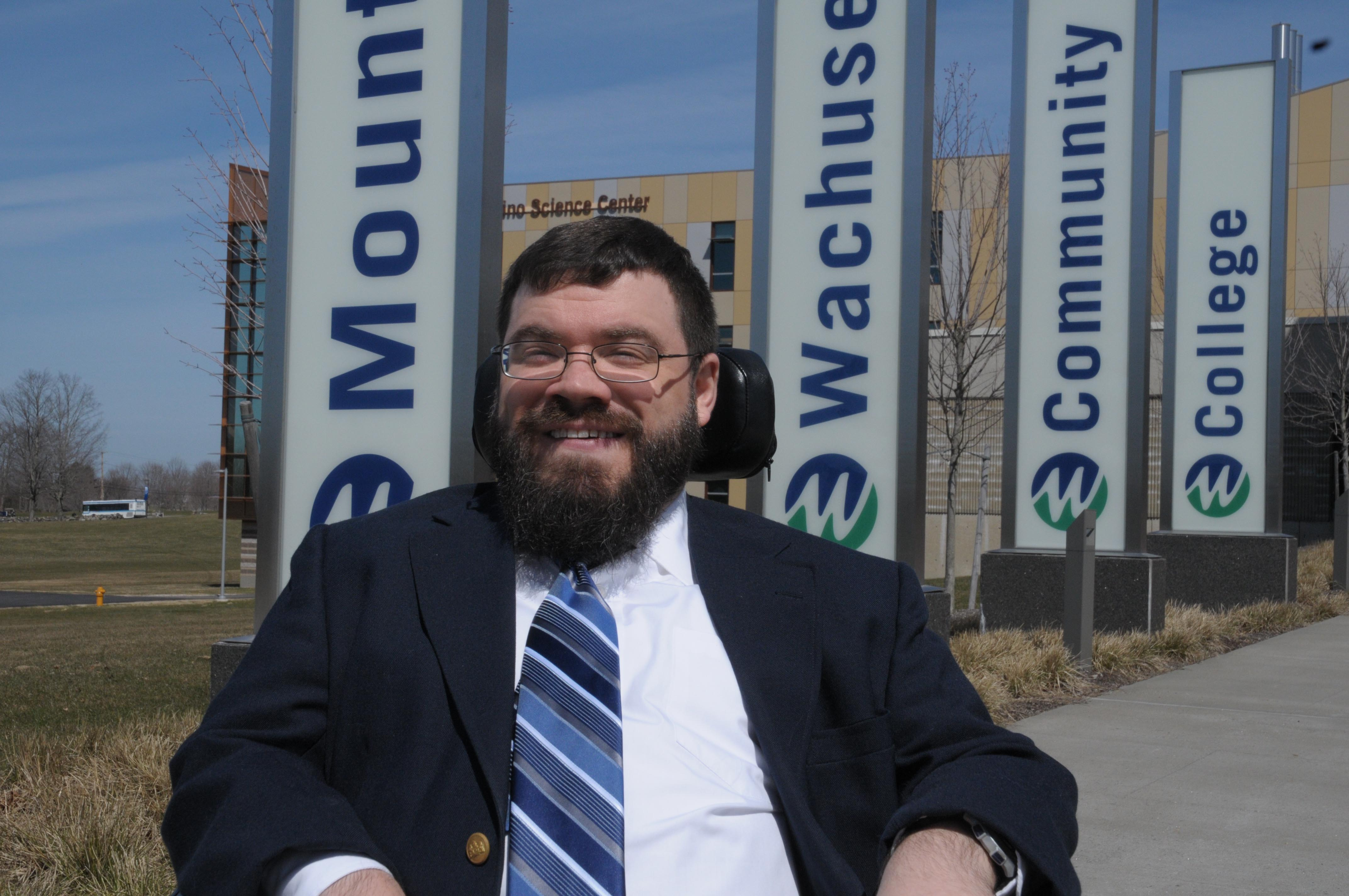 Nate Johnson sits in front of signs outside of Mount Wachusett Community College.