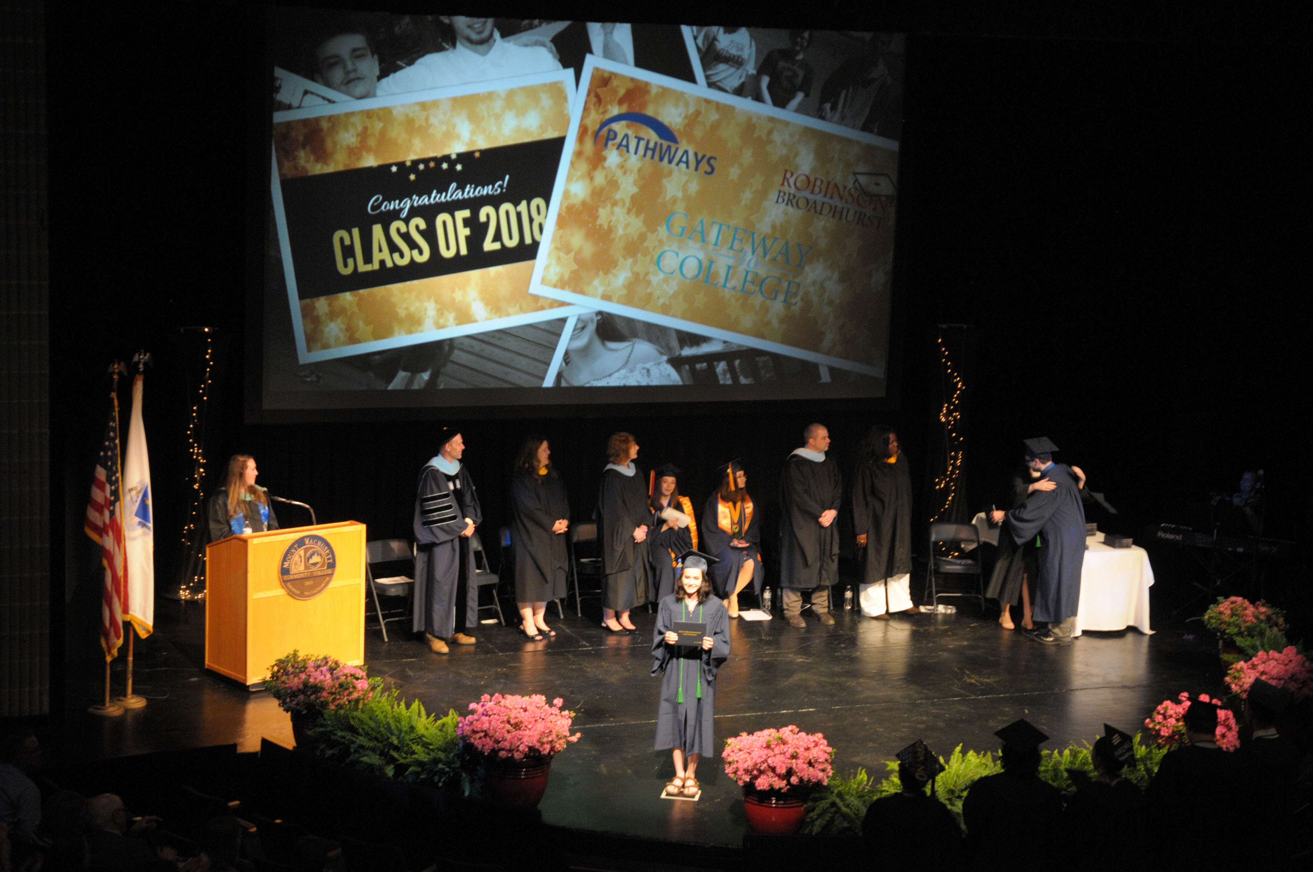 A student holds her diploma on stage with other people standing at the back of the stage.
