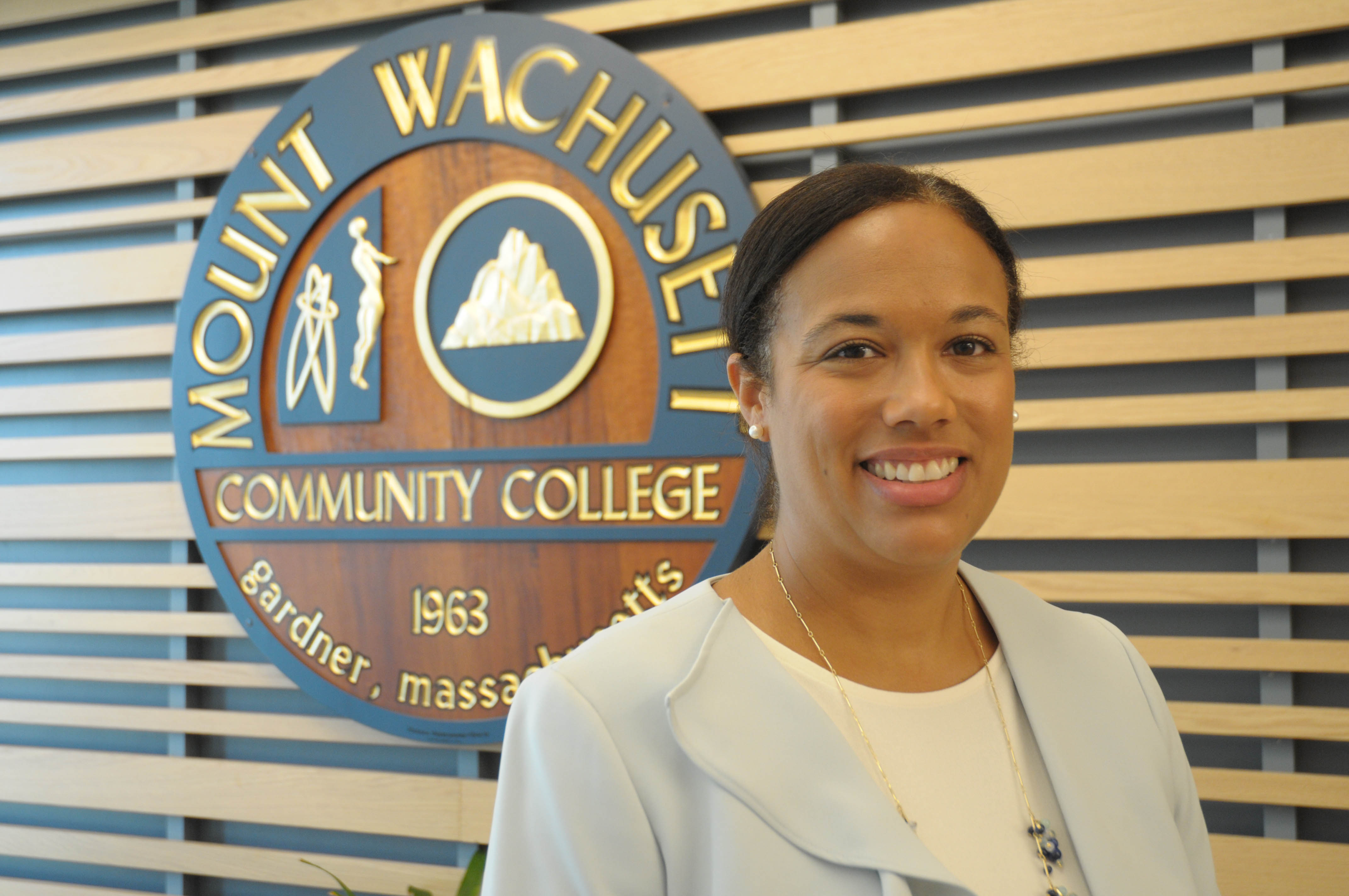 Jamy Gaynor poses in front of the MWCC seal.