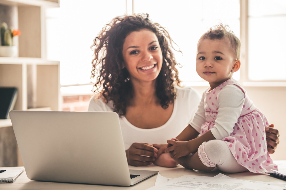 Photo of mother with child and laptop