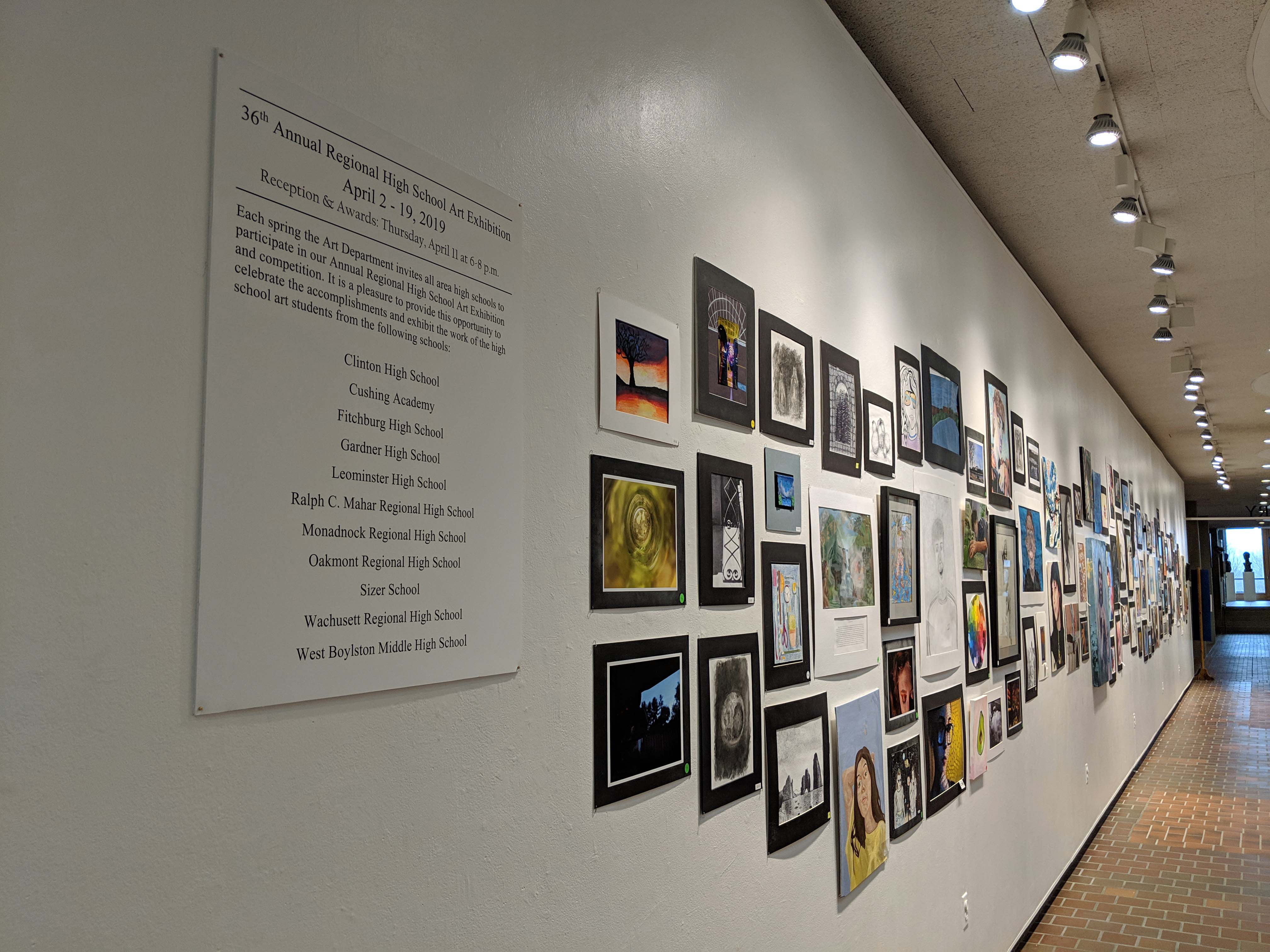 A wall covered with paintings is shown.