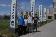 Four students stand outside a building.