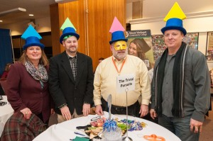 """""""The Trivial Pursuits"""" team, four members with Trivial Pursuit pieces on their hats"""